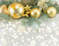 Yellow christmas tree decorations and a fir brach Royalty Free Stock Photography