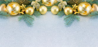 Yellow christmas tree decorations and a fir brach Royalty Free Stock Image