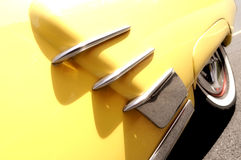 Yellow and chrome classic car. A view of the rear wheel and fender of a classic automobile with chrome flares and a white wall tire Stock Photos