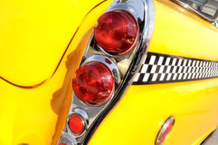 Yellow and chrome classic taxi cab. A view of the rear tail light and fender of a classic taxi automobile with a checkered stripe Royalty Free Stock Photo