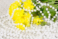 Yellow chrysanthemums and beads are pearls Stock Images