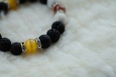 Yellow Chrysoberyl Cat`s Eye stone and Lava stone.Luck fortune stone bracelet with yellow and black tone on white wool background. Amulet accessories for good royalty free stock photography