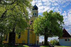 Yellow church in lush park at sunny day in spring royalty free stock photography