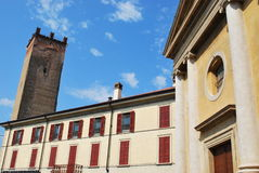 Yellow church and medieval tower. Yellow church facade and medieval tower in Castelleone, Cremona, Italy Royalty Free Stock Photos
