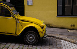 Yellow Citroen 2CV in front of Yellow Building. Yellow classic car Citroen 2CV parked in front of a building with a yellow facade in Vienna, Austria Stock Images