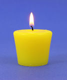 Yellow citronella candle. A new insect repellent citronella candle that is lit on a blue background Royalty Free Stock Photos