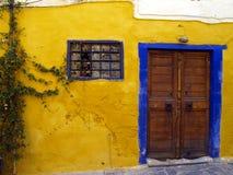 Yellow cladding. Of old cretan house, wooden door, barred window Royalty Free Stock Photos