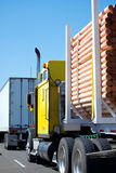 Yellow classic big rig semi truck transports processed round log. A classic simple powerful bright yellow big rig semi truck with long cab intended for long haul stock photography