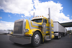 Yellow classic custom semi truck with two bulk trailers. The classic yellow powerful American heavy big rig semi truck with chrome accents and individually royalty free stock photo