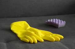 Yellow cleaning gloves and a sponge on the couch, close-up screen royalty free stock image