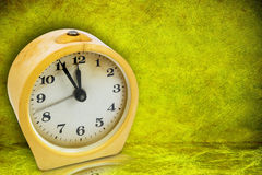 Yellow clock on green background Royalty Free Stock Photos