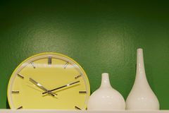 A yellow clock and two white bottles with green background Stock Photography