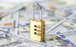 Yellow closed padlock and dollars Royalty Free Stock Images