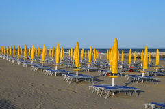 Yellow closed Sun umbrellas on sea beach with sun loungers Stock Images