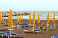Yellow closed Sun umbrellas on sea beach with sun loungers Stock Photo