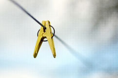 Yellow clothes peg on a washing line. Closeup of Colorful clothes peg on a rope isolated on light backgroundrr royalty free stock photos