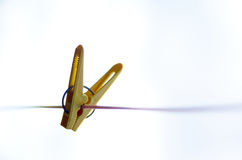 Yellow clothes peg on a washing line. Closeup of Colorful clothes peg on a rope isolated on light backgroundrr stock photo