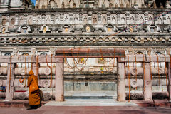 Yellow clothing monk walk past the stone temple Stock Image
