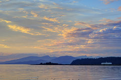 Yellow clouds reflecting on sea water at sunset Royalty Free Stock Photography