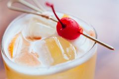 Yellow cocktail filled a sliced of lemon and ice that served with fresh cherry on wooden table Stock Photo