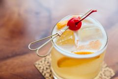 Yellow cocktail filled a sliced of lemon and ice that served with fresh cherry on wooden table Stock Image