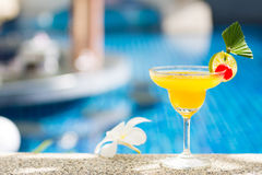 Yellow cocktail with lime by the pool Stock Image