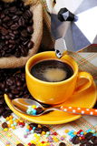 Yellow coffee cup with coffee maker. Yellow coffee cup with jute sack and coffee maker on colorful background with colored sugar pearls Royalty Free Stock Image