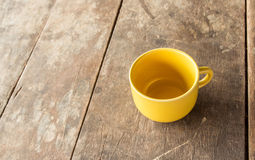 Yellow coffee cup on old wooden table Stock Photography