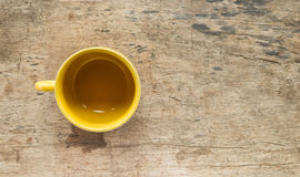 Yellow coffee cup on old wooden table Stock Photos