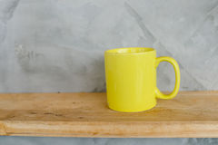 Yellow coffee cup on wooden shelf Stock Photos