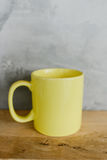 Yellow coffee cup on wooden shelf - Stock Images