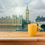 Yellow coffee cup on wooden table over London Big Ben Royalty Free Stock Images