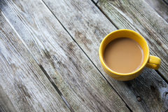 Yellow coffee mug on a rustic wooden table. Looking down on a coffee mug with coffee with cream on a rustic tabletop background royalty free stock photos