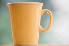 Yellow coffeecup. Yellow coffee cup with green bokeh Stock Image