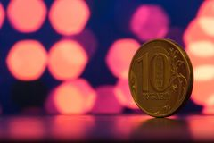 Yellow coin on a background of pink bokeh. Russian ruble close up on a background of purple bokeh Royalty Free Stock Photography