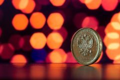 Yellow coin on a background of orange bokeh. Russian ruble close up on a background of purple bokeh Royalty Free Stock Photo