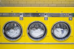 Yellow coin washing machines with laundry in it stock photography