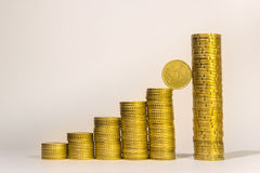 Yellow coins lined up from short to tall stacks Stock Photos