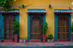 Yellow colonial house front with three doors. On the streets of Cartagena, Colombia Royalty Free Stock Photography