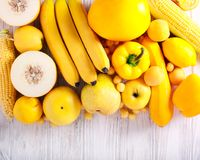 Yellow color assorted vegetables and fruits. On wooden table stock image