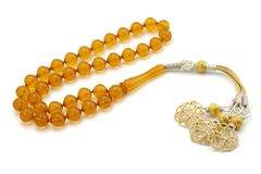 Yellow color bakelite rosary prayer beads isolated on white. Handmade orange colored transparent bakelite prayer beads with silver tassel isolated on white royalty free stock photo