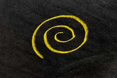 Yellow color chalk hand drawing as spiral shape on black board background. Abstract, design, swirl, circle, pattern, element, helix, curve, twirl, hypnosis royalty free stock images