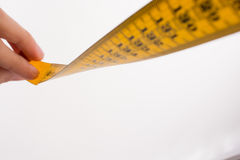 Yellow color measuring tape in hand Royalty Free Stock Photography