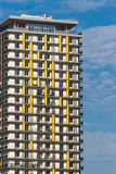 Yellow colored apartment building at noon against blue sky. Royalty Free Stock Images