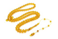 Yellow colored bakelite rosary beads isolated on white. Transparent yellow colored bakelite rosary prayer beads isolated on white background. Islamic religious royalty free stock photography