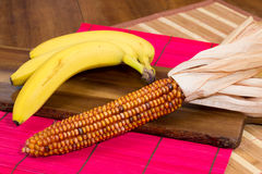 Yellow colored corn and three bananas on a wooden board Stock Photo