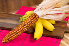 Yellow colored corn and three bananas on a wooden board Royalty Free Stock Photo