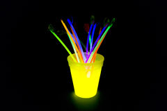 Yellow colored fluorescent glass with glow sticks lights. Yellow fluorescent glass with glow sticks neon light on back background. variation of different colored Royalty Free Stock Photo
