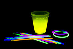 Yellow colored fluorescent glass with glow sticks lights. Yellow fluorescent glass with glow sticks neon light on back background. variation of different colored Stock Photography