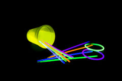 Yellow colored fluorescent glass overturned with glow sticks lights. Yellow fluorescent glass fallen with glow sticks neon light on back background. variation of Stock Photos